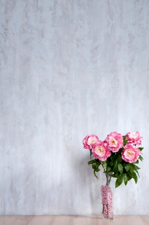 Bouquet of peonies in a vase against a blue wall. Interior. Archivio Fotografico