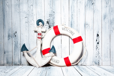 antique furniture: Anchor and life buoy on a background of white shabby wall boards.