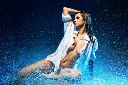 Young topless girl in the rain. Water studio photo.