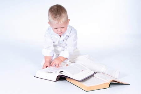 Little business man in solid white suit reads books photo