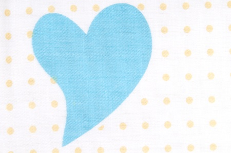 Blue heart on a white background with dots. Pattern on the fabric.