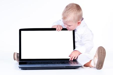 Niño pequeño negocio en traje sólido blanco que se sienta en el cuaderno en un fondo blanco Foto de archivo - 17787901