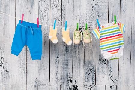 ropa colgada: Ropa de beb? colgando de la cuerda. Foto de archivo