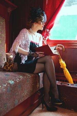 Retro girl reading book in  wagon train Stock Photo