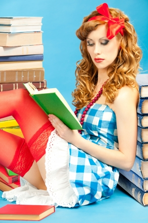 Pretty smart beautiful pin up  girl reads book Фото со стока