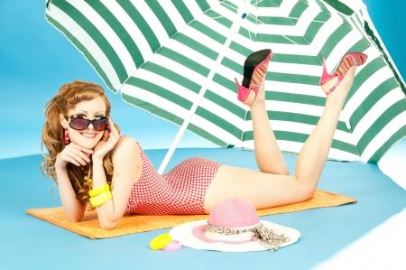 Beautiful sexy girl pin up in a bright bikini resting, tans on the beach under sun umbrella Archivio Fotografico