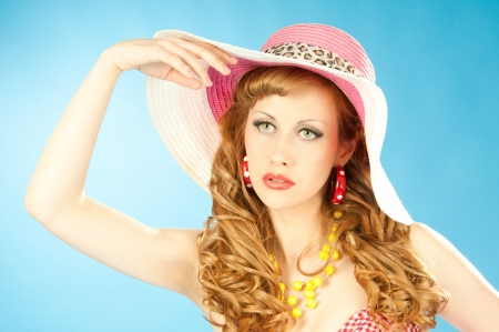 A large portrait of a cute red-haired girl in the pink sun hat