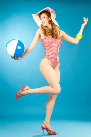Laughing beautiful girl pin-up in a pink bikini with beach ball
