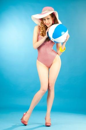 Smiling beautiful girl pin-up in a pink bikini with beach ball