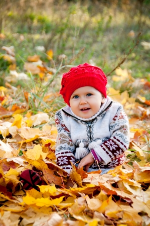 coif: Little cute baby girl on a background of autumn leaves