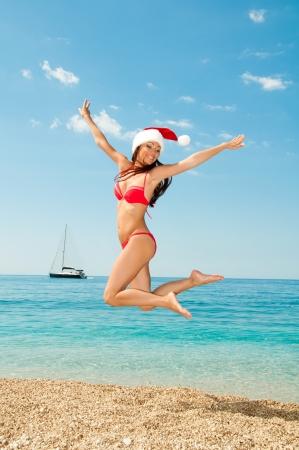 Santa chica en traje de baño y sombrero contra el mar. En el salto. Foto de archivo - 23820073