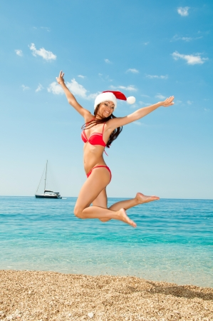 Santa girl in a bathing suit and hat against the sea. In the jump.