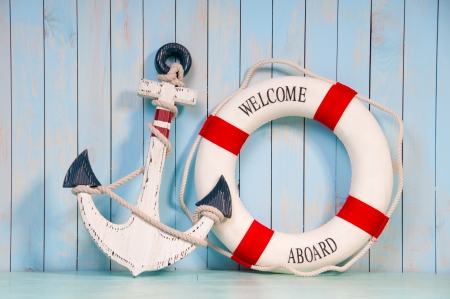 Anchor and life buoy on white shabby wall boards. Stockfoto