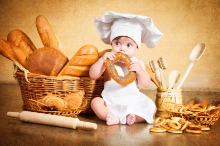 Little cook with a bagel in her hands.