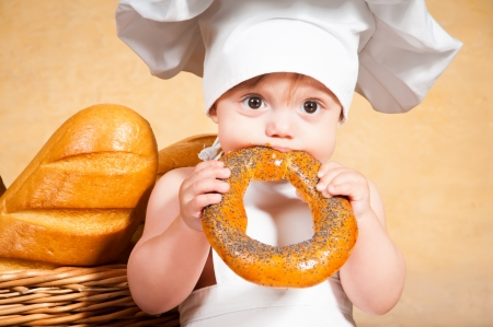 Little cook with a bagel in her hands. photo