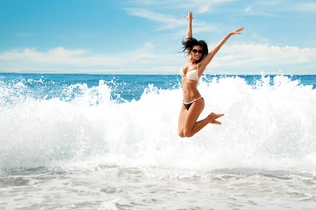 Beautiful young  girl  jumping into sea Фото со стока