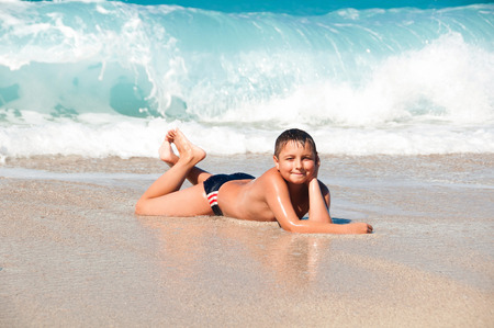 Boy at the sea lying on the sand and waves Stock Photo