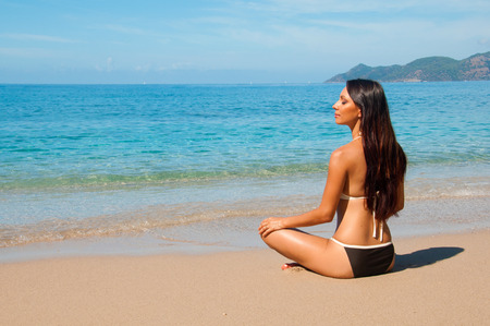 Brunette sitting on the beach in a lotus position Stockfoto