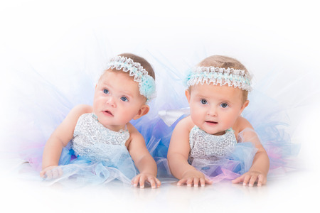 Two charming sisters baby twins in the lush beautiful dresses Archivio Fotografico