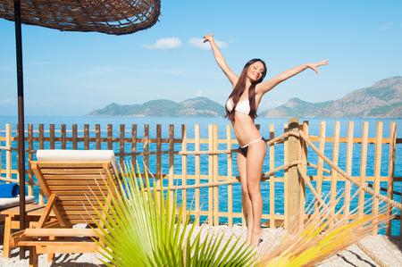 on tiptoes: Girl on tiptoes enjoys sun and sea