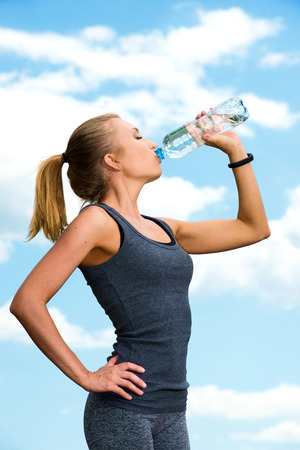 recuperation: Fitness beautiful blonde woman drinking  water after sports on the background of sky and clouds