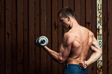 powerfully: Young athletic man doing workout with heavy dumbbell
