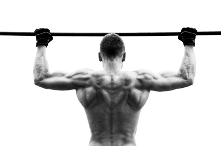 gripping bars: Muscle man making pull-up on horizontal bar against the sky