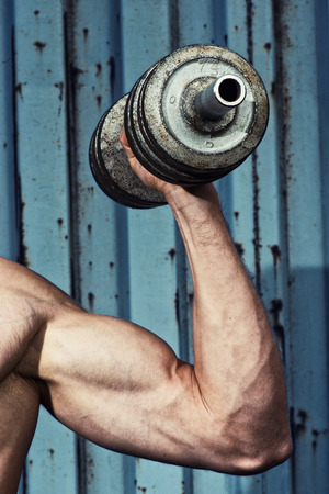 powerfully: Muscular arm with dumbbell close up Stock Photo