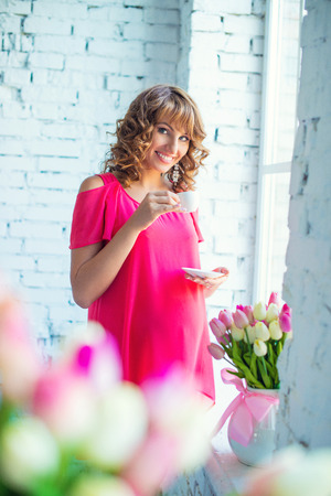 childbearing: Tender pregnant girl in bright pink dress at the window with morning coffee