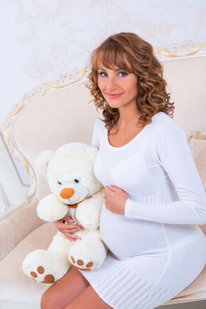 firstborn: Close-up pregnant girl in knit dress with teddy bear