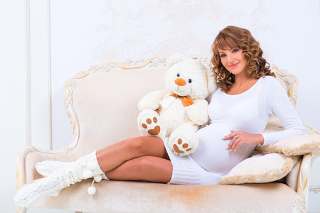 firstborn: Redheaded pregnant girl in a knitted dress with teddy bear on the couch
