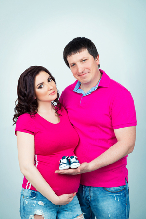 firstborn: Smiling beautiful pregnant couple in crimson shirt with baby booties in hands