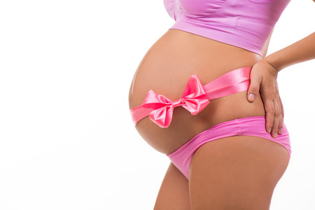 bow belly: Close portrait of a pregnant belly with pink satin bow isolated on white background. Horizontal