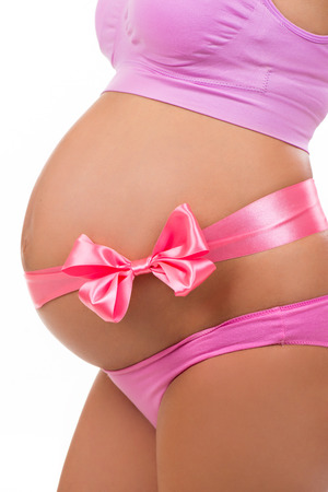 bow belly: Close portrait of a pregnant belly with pink satin bow isolated on white background. Vertical Stock Photo