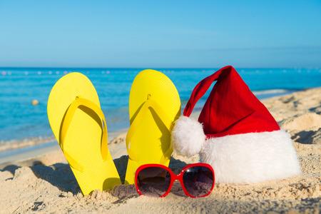 beach happy new year: Christmas vacation at sea. Happy  New Year holidays. Santa hat, sandals, sunglasses on sandy beach Stock Photo