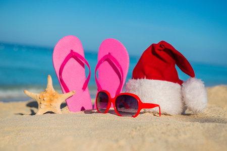 beach happy new year: Happy  New Year holidays and Merry Christmas at Sea. Sandals, sunglasses and santa hat on sandy beach. Stock Photo