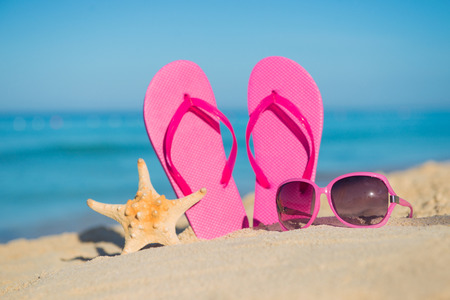 resort beach: The sea, beach, sand and womens accessories: pink flip-flops, sunglasses and starfish Stock Photo
