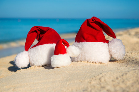 santa hat: Santa hats on sandy beach  - concept of New Year family holiday with the children on the sea.