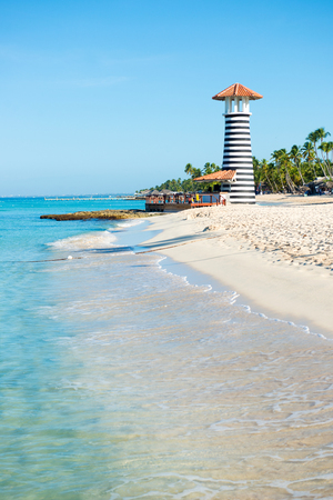 pharos: Beautiful day at sea. White sand, tropical palm trees and lighthouse on sandy shore Stock Photo