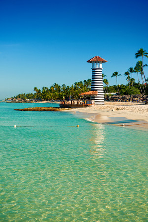 cerulean: Striped lighthouse on sandy shore with palm trees. Clear water of the Caribbean sea. Stock Photo