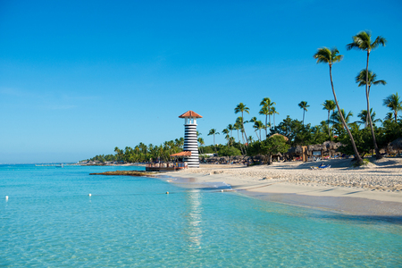 cerulean: Transparent sea water and clear sky. Lighthouse on a sandy tropical island with palm trees.