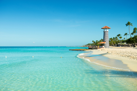 Paradise Caribbean landscape. Clear sea, white sand, tropical palm trees and lighthouse on sandy shore