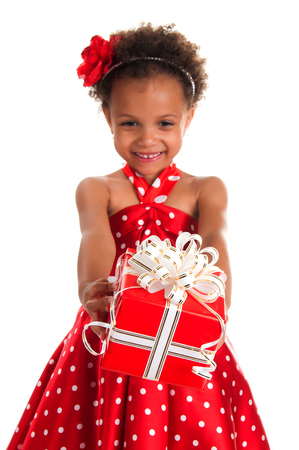 dar un regalo: niña sonriente con el pelo rizos dan una caja de regalo en las manos. Feliz Año Nuevo y vacaciones de Navidad Foto de archivo