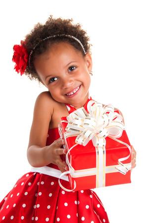 dar un regalo: ni�a sonriente con el pelo rizos dan una caja de regalo en las manos. Feliz A�o Nuevo y vacaciones de Navidad Foto de archivo