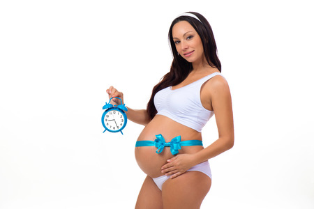 9 months: 9 months. Happy pregnancy. Pregnant woman with alarm clock in his hands and blue bow on the tummy