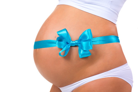 bow belly: Close-up of pregnant belly with  blue ribbon and bow. Concept of pregnancy. Newborn baby boy. Stock Photo