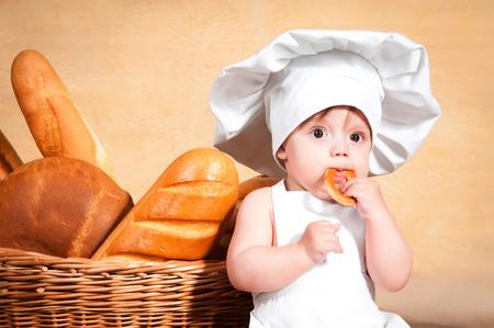 comiendo pan: Poco cocina en el sombrero de un cocinero comer un bagel. Retrato de primer plano.