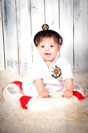 lifebelt: Funny smiling little boy dressed as a sea captain in naval cap. Marine decor, lifebelt.