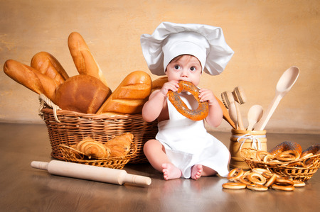 pastry chef: Little cook. Small kid in a chefs hat with wicker baskets of pastries, rolls, bread and bagels Stock Photo