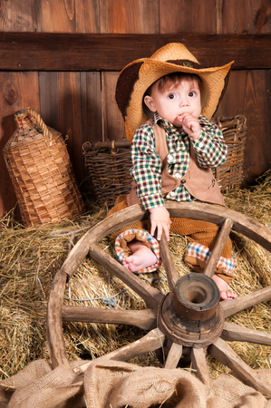 racy: Little boy in cowboy hat, a waistcoat and a plaid shirt sitting in the hay